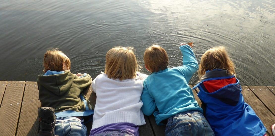 children laying on dock overlooking water