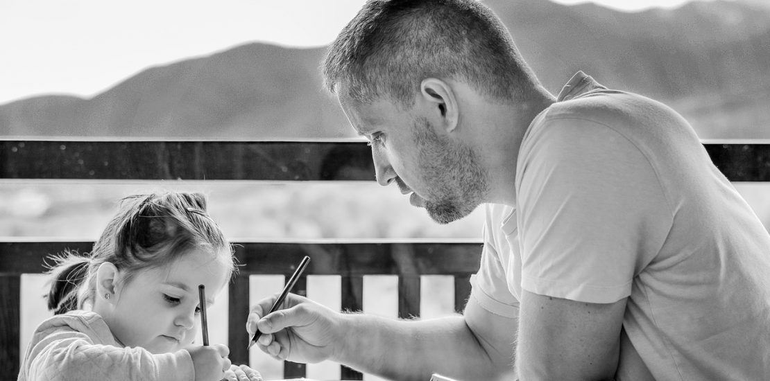 girl and father drawing together