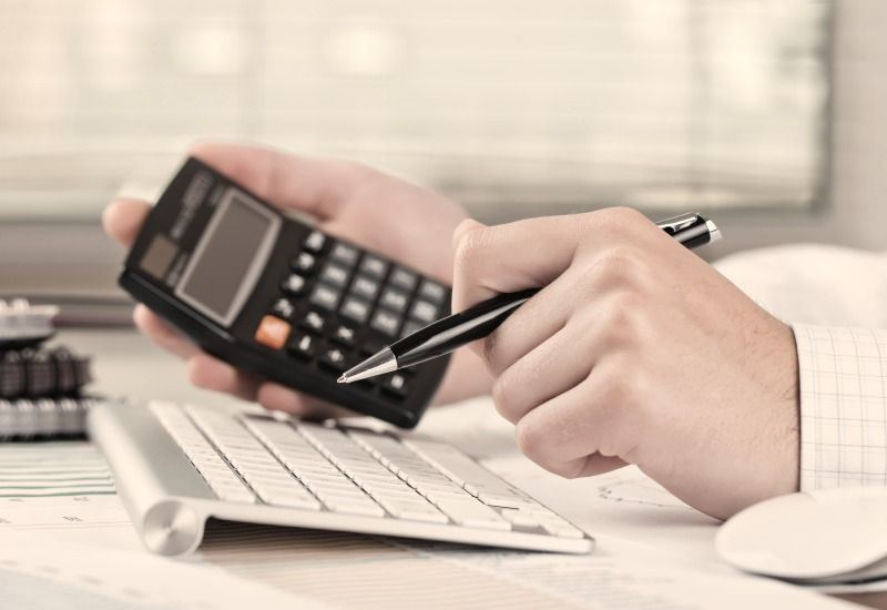 man making calculations using calculator