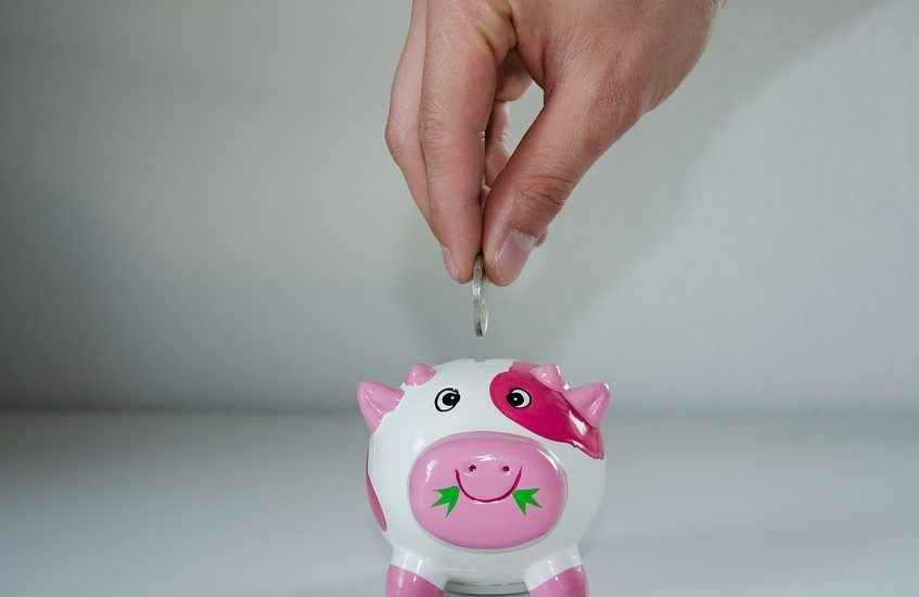 adding coin to pink piggy bank