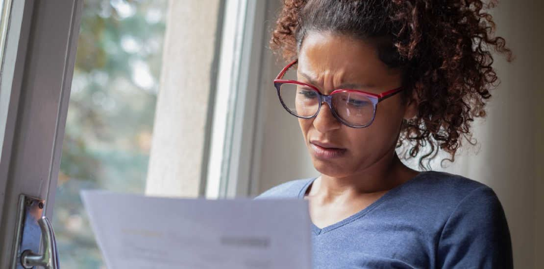 woman looking at paperwork with a worried look on her face